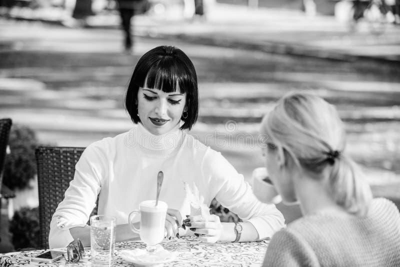 Amigas bebem café conversas Mulheres de conversa em terraço de café Relações amigáveis de amizade Revelação e apoio imagens de stock