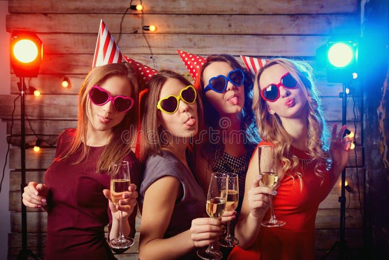 Amigas da festa de anos Meninas bonitas nos tampões, e colorido fotos de stock royalty free