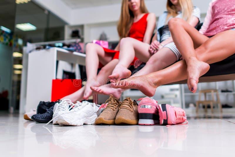 Amigas de sorriso novas que sentam-se em uma loja de roupa que olha seus pés desencapados e pilha de sapatas novas e do riso foto de stock royalty free