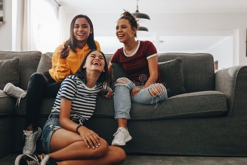 Amigas en casa que miran la televisión imágenes de archivo libres de regalías