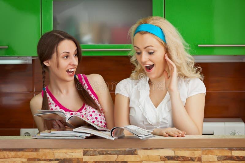 Amigas engraçadas que consultam compartimentos na cozinha fotos de stock royalty free