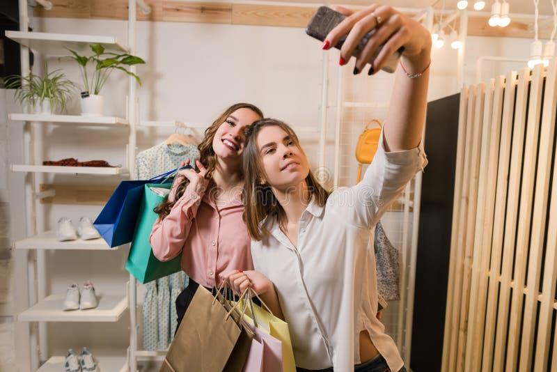 Amigas felizes que fazem o selfie com sacos de compras imagens de stock