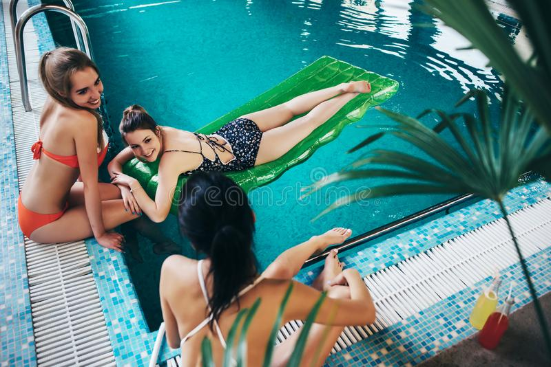Amigas novas que vestem o roupa de banho que relaxa na piscina que fala e que sorri fotografia de stock