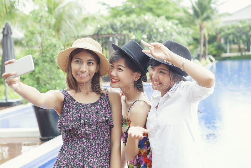 Amigo asiático de una mujer más joven que toma fotografía por el hap elegante del teléfono fotos de archivo libres de regalías