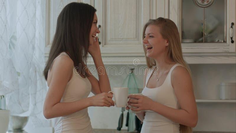 Amigo de dos muchachas con café de consumición del teléfono o té verde en fondo del interior de la cocina imagen de archivo