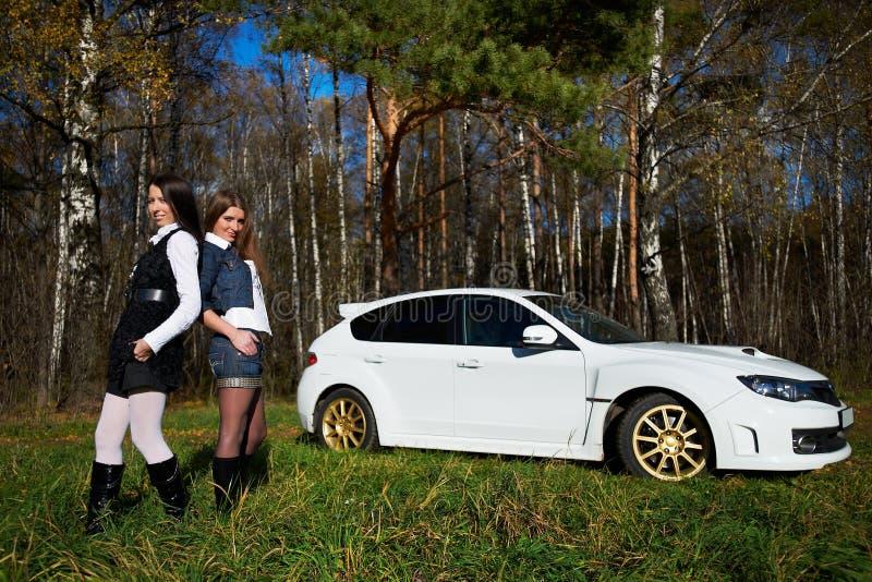 Amigo de duas meninas e carro de esportes branco à moda imagem de stock royalty free