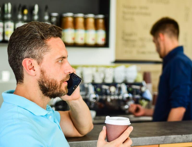 Amigo de la llamada para tener bebida junto El individuo ocupado habla el teléfono mientras que relaje el descanso para tomar caf imágenes de archivo libres de regalías