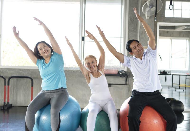 Amigo del grupo del mayor en el gimnasio de la yoga que se sienta en su bola que sonríe y feliz forma de vida sana mayor imagen de archivo