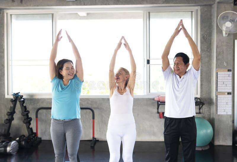 Amigo del grupo del mayor en el gimnasio de la yoga que sonr?e y feliz forma de vida sana mayor imagen de archivo libre de regalías