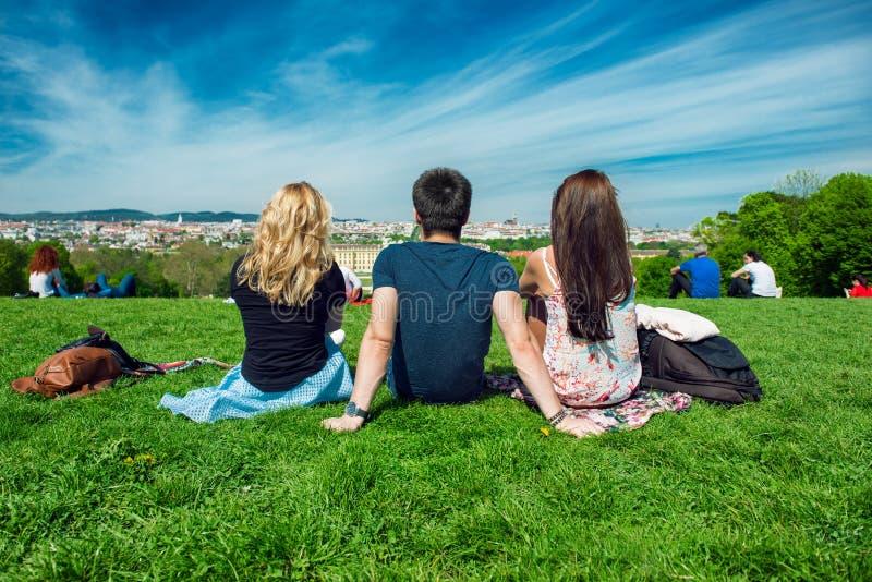 Amigo dos turistas que senta-se na grama verde com vista bonita ao panorama de Viena fotografia de stock