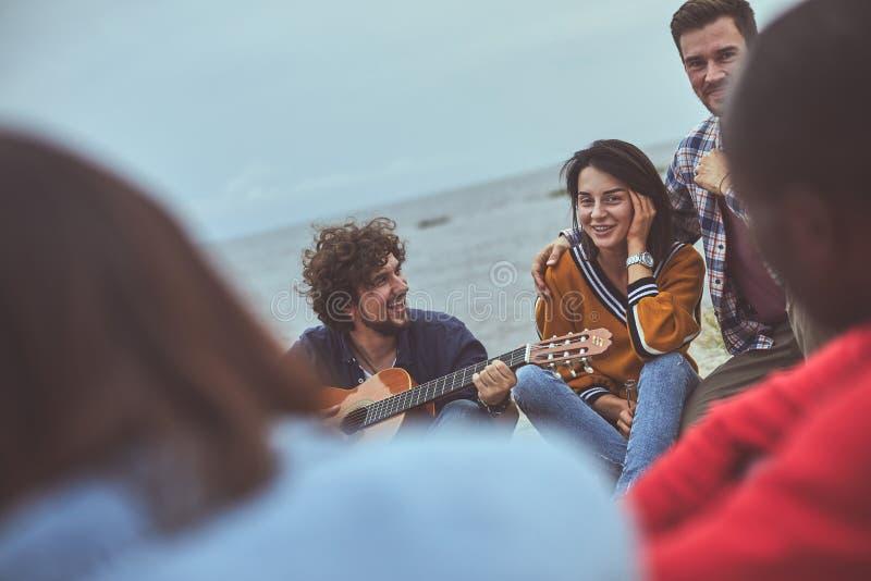 Amigo que joga a guitarra no litoral foto de stock royalty free