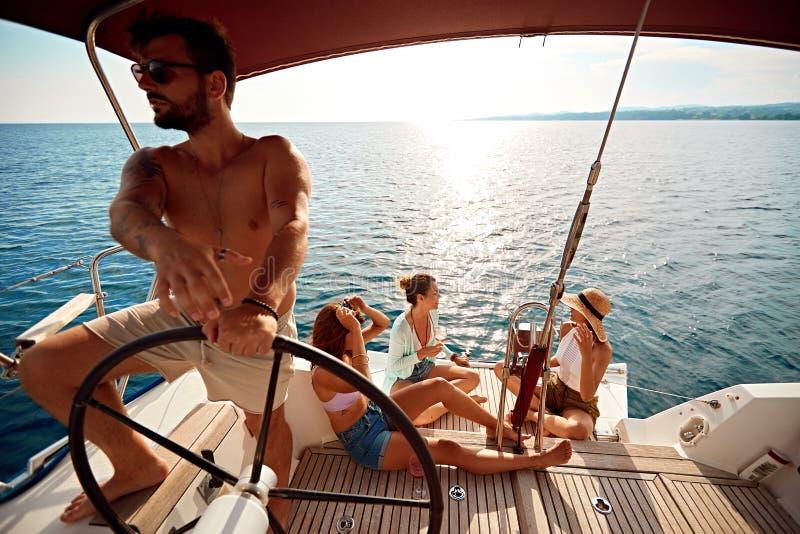 Amigo que tem o partido no barco de navigação em férias foto de stock