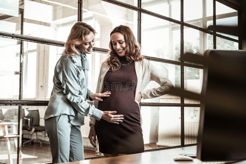 Amigo rubio de emisión que frota el vientre embarazada de su colega oscuro-cabelludo imagen de archivo libre de regalías