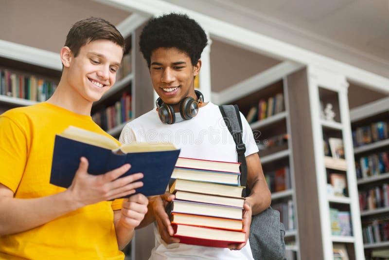 Amigos adolescentes diversos que discutem o livro na biblioteca foto de stock