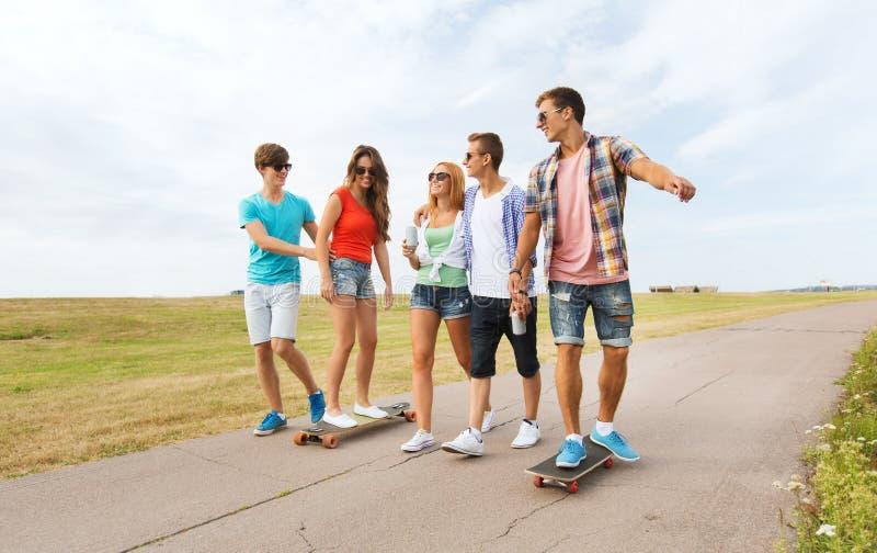 Amigos adolescentes felices con longboards al aire libre fotos de archivo