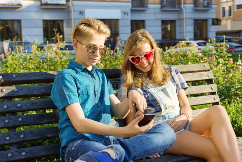 Amigos adolescentes muchacha y muchacho que se sientan en banco en la ciudad, hablando Amistad y concepto de la gente fotografía de archivo libre de regalías