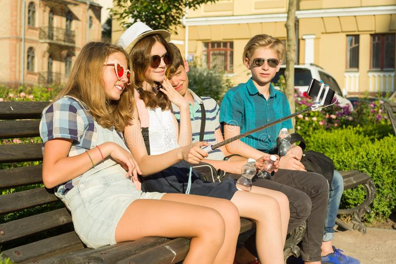 Amigos adolescentes muchacha y muchacho que se sientan en el banco en la ciudad, hablando, mirando en el teléfono, haciendo la fo imagen de archivo libre de regalías