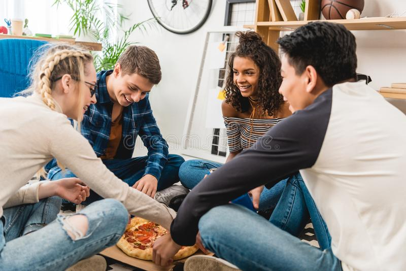 amigos adolescentes multiétnicos que se sientan en piso imagen de archivo libre de regalías