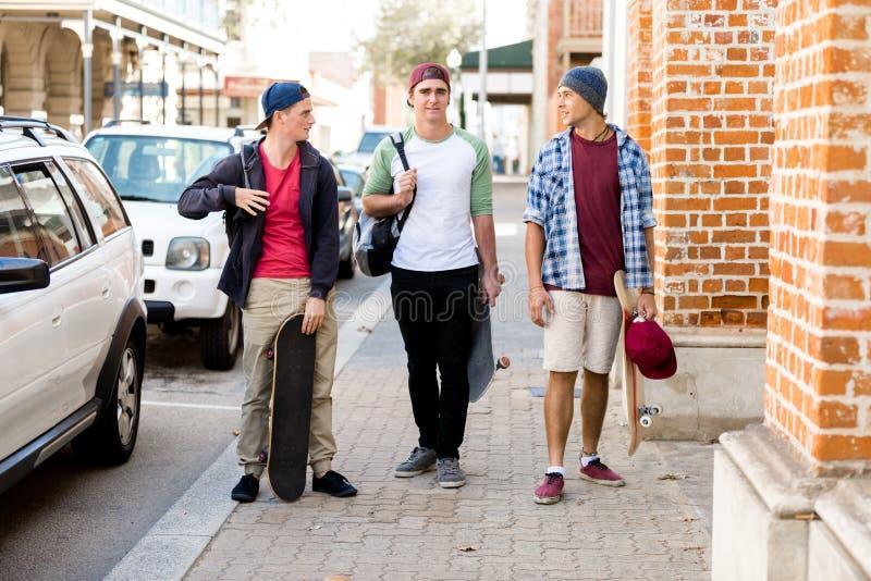 Amigos adolescentes que caminan en la calle imagenes de archivo