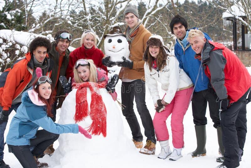 Amigos adolescentes que constroem o boneco de neve no jardim fotos de stock royalty free