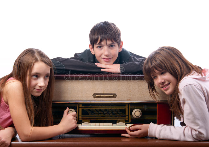 Amigos adolescentes que escutam a música no rádio velho fotografia de stock