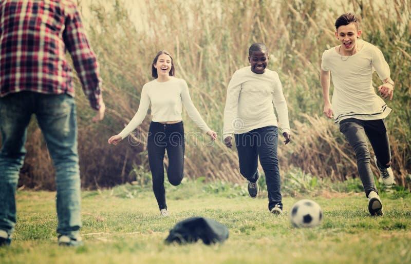 Amigos adolescentes que juegan a fútbol fotografía de archivo