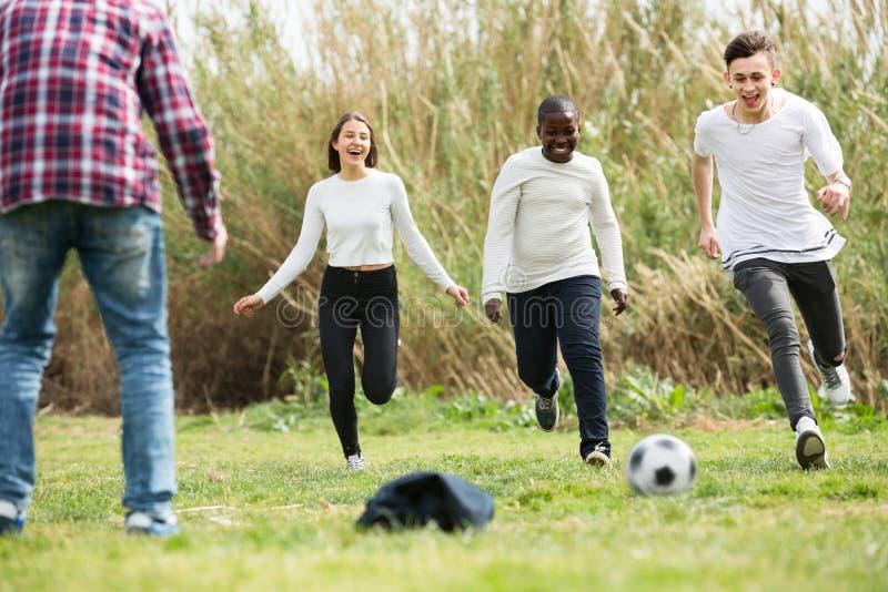 Amigos adolescentes que juegan a fútbol foto de archivo libre de regalías