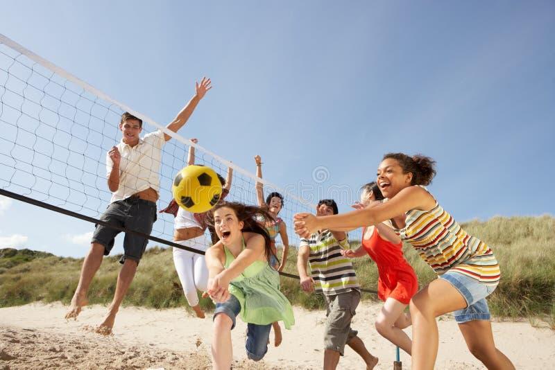 Amigos adolescentes que juegan a voleibol en la playa imagenes de archivo