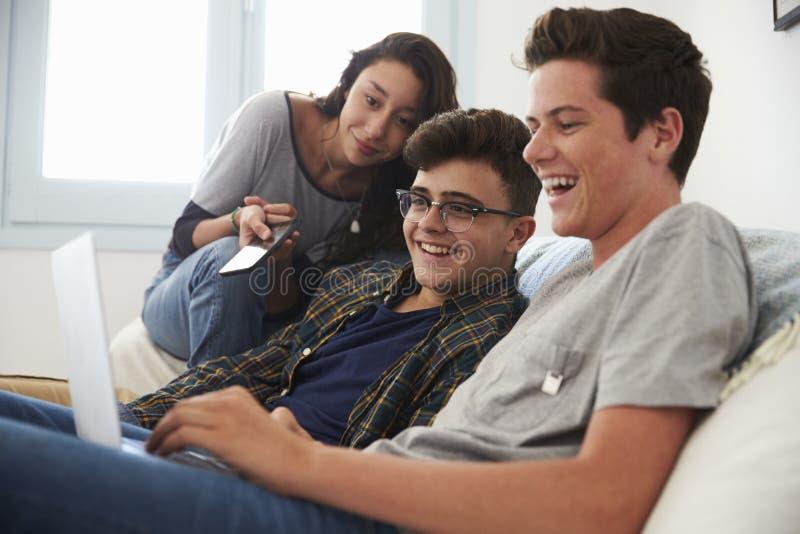 Amigos adolescentes que miran algo divertido en el ordenador portátil foto de archivo libre de regalías
