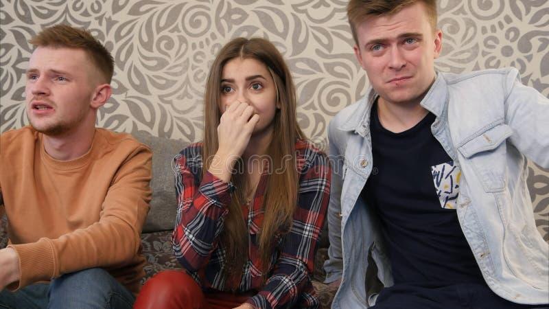 Amigos adolescentes que miran película asustadiza en la televisión y que cierran ojos y caras del coverng fotografía de archivo