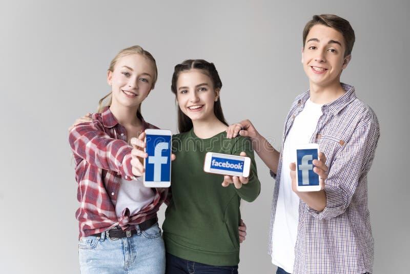 Amigos adolescentes que muestran smartphones con el logotipo del facebook aislado en gris fotografía de archivo