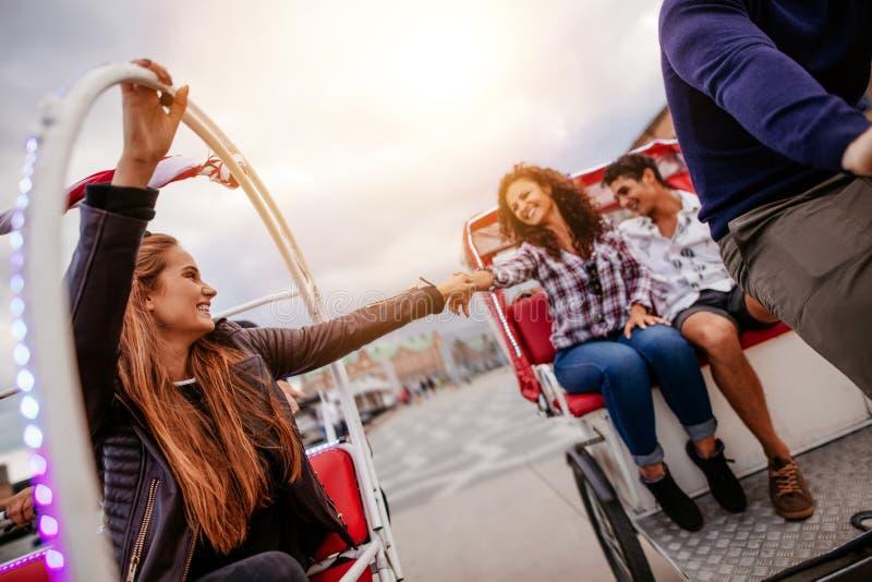 Amigos adolescentes que se divierten en los triciclos imágenes de archivo libres de regalías