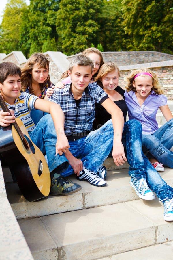 Amigos adolescentes que sentam-se em escadas imagens de stock