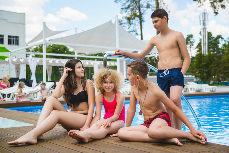 Amigos adolescentes que sentam-se na borda de uma piscina imagem de stock