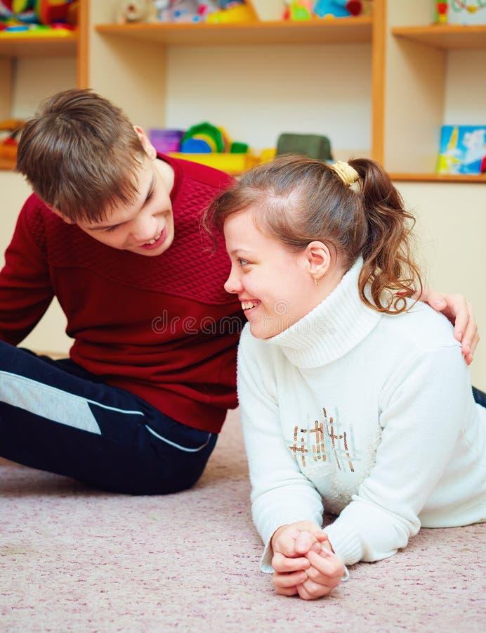 Amigos adolescentes sonrientes con necesidades especiales que hablan alegre junto en centro de rehabilitación fotografía de archivo