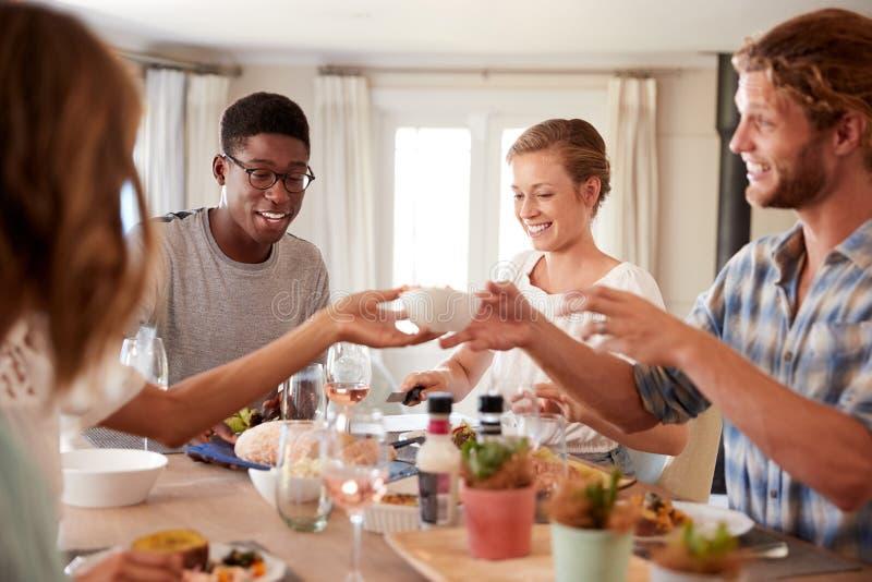 Amigos adultos novos que passam um prato através da tabela de jantar no almoço, fim acima imagens de stock royalty free