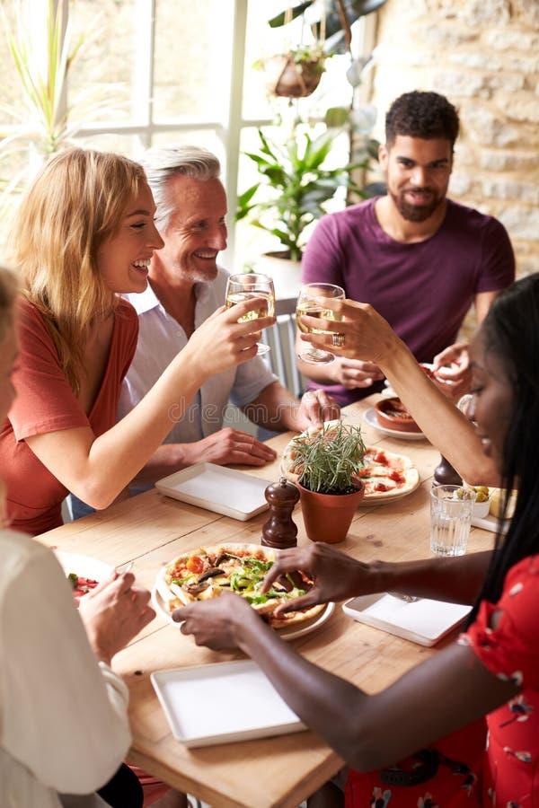 Amigos adultos que comen en un café que hace una tostada, vertical foto de archivo