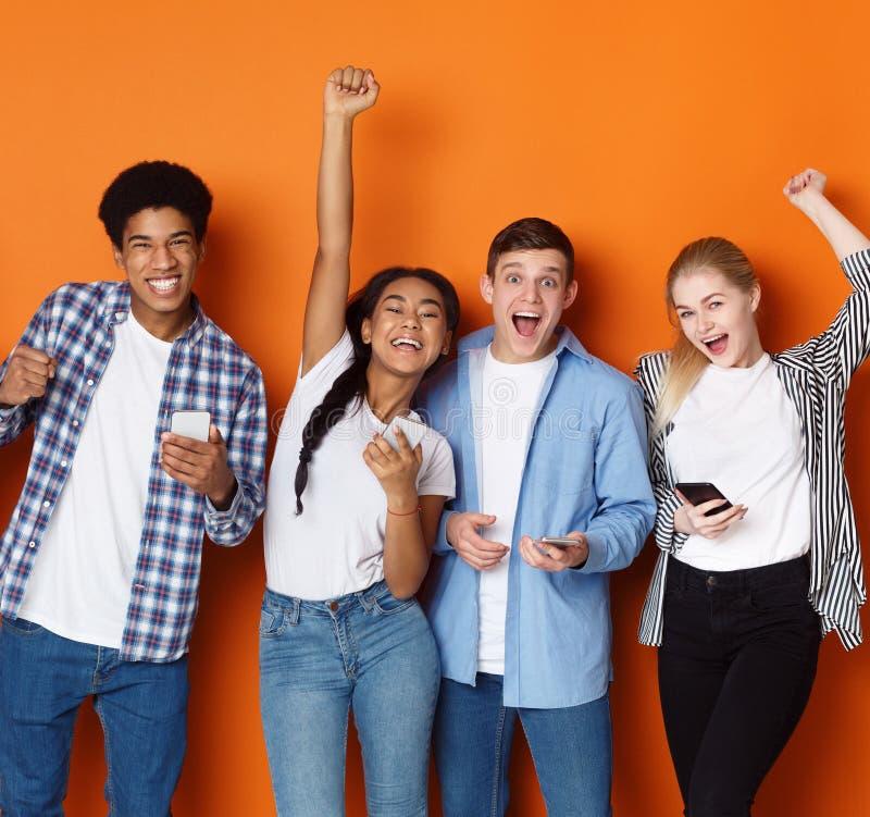 Amigos afortunados Estudiantes con los tel?fonos que gritan sobre fondo imágenes de archivo libres de regalías