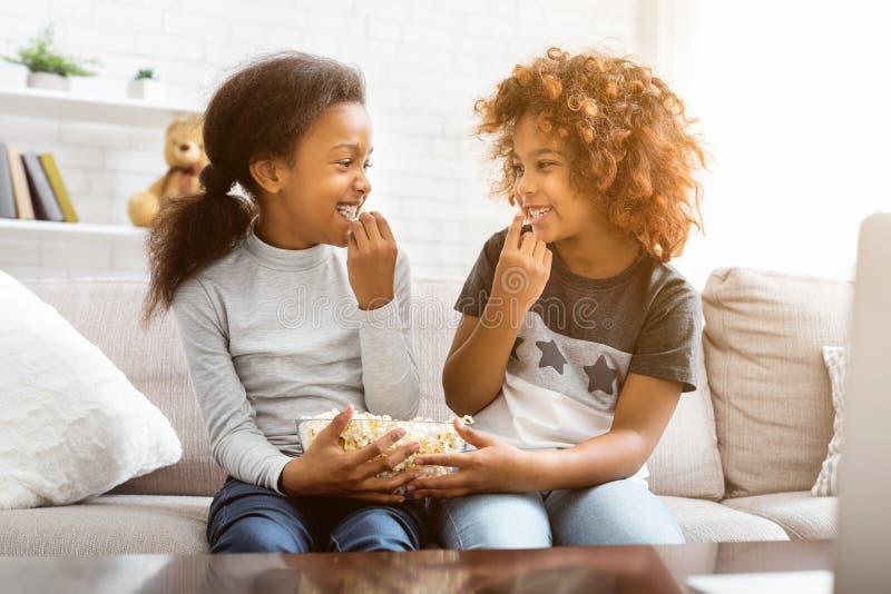 Amigos afro-americanos que comem a pipoca, olhando se imagens de stock
