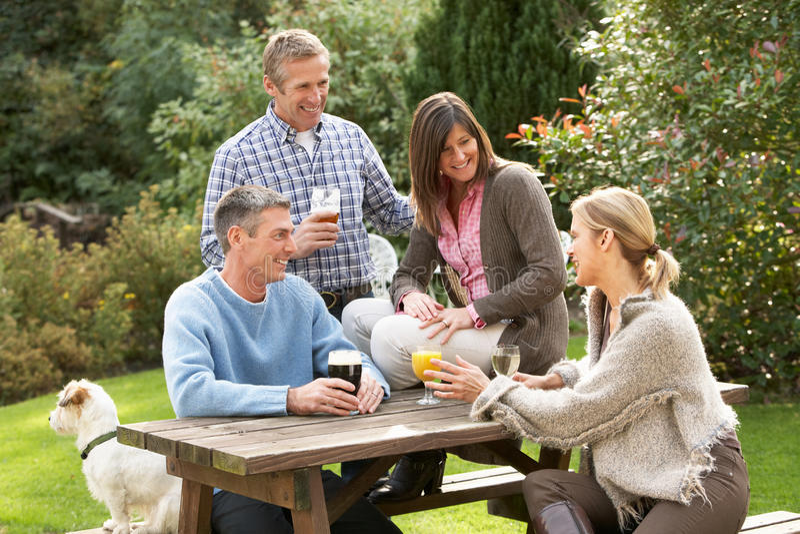Amigos al aire libre que disfrutan de la bebida en jardín del Pub fotografía de archivo libre de regalías