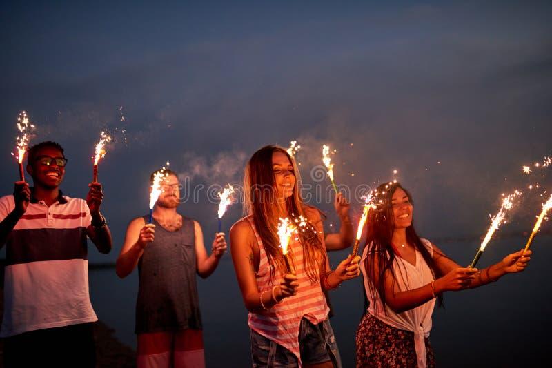 Amigos alegres con las bengalas en la playa del verano imagenes de archivo