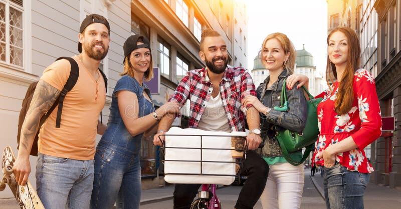 Amigos alegres del inconformista que presentan en el centro de la ciudad en las calles foto de archivo