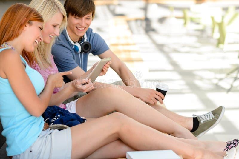 Amigos alegres do estudante que usam a tabuleta junto fotografia de stock