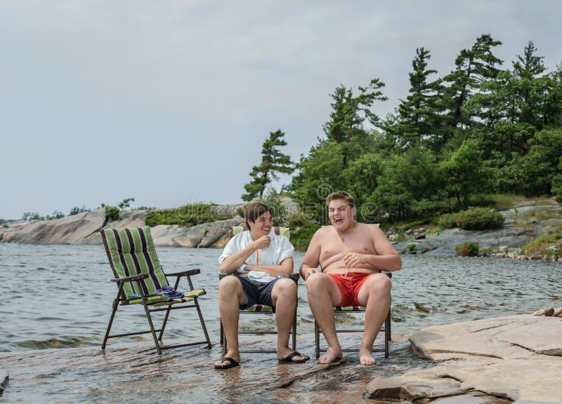 Amigos alegres engraçados que falam o relaxamento de riso no parque perto do lago imagem de stock royalty free