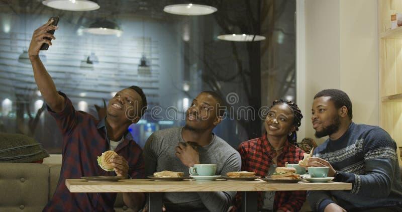 Amigos alegres negros que disfrutan del encuentro en café fotos de archivo