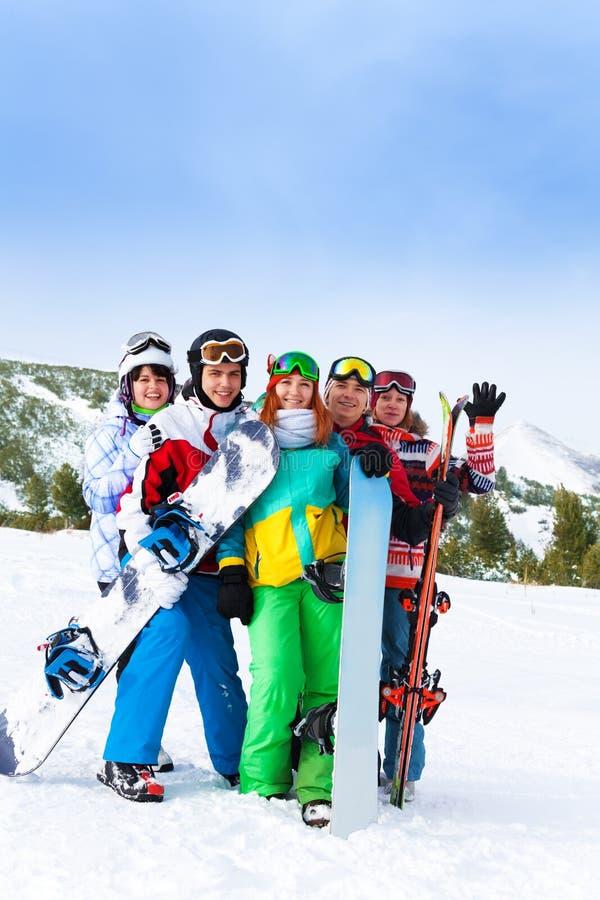 Amigos alegres que estão com snowboards imagem de stock