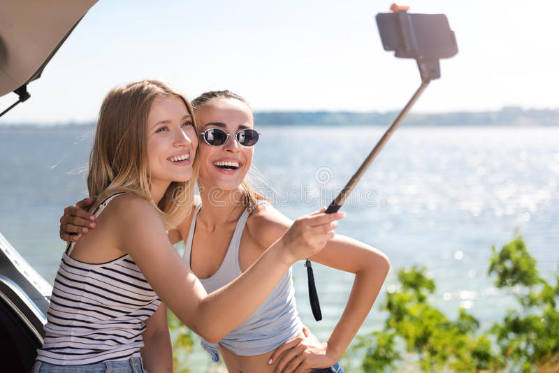 Amigos alegres que fazem selfies imagens de stock royalty free