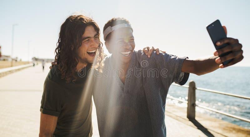 Amigos alegres que hacen un selfie en una 'promenade' de la playa imagen de archivo libre de regalías