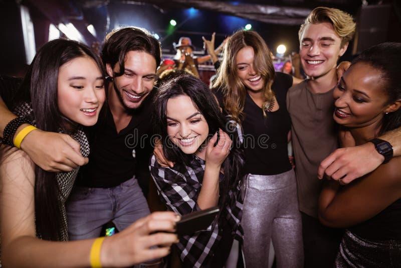 Amigos alegres que miran el teléfono móvil mientras que goza en el club nocturno foto de archivo libre de regalías