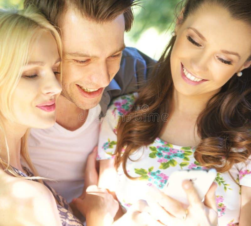 Amigos alegres que prueban el nuevo teléfono móvil fotos de archivo